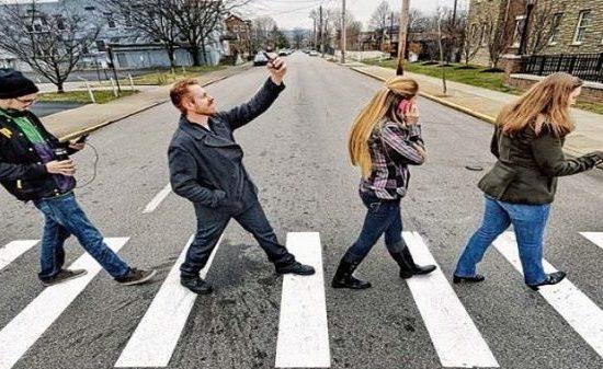 peatones caminan con celulares